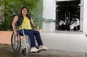 Mulher cadeirante a frente na entrada da biblioteca do centro de humanidades