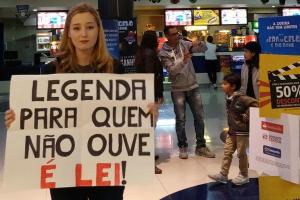 """A estudante surda Danielle Kraus segurando um cartaz em um cinema onde se lê: """"legenda para quem não ouve é Lei!"""""""